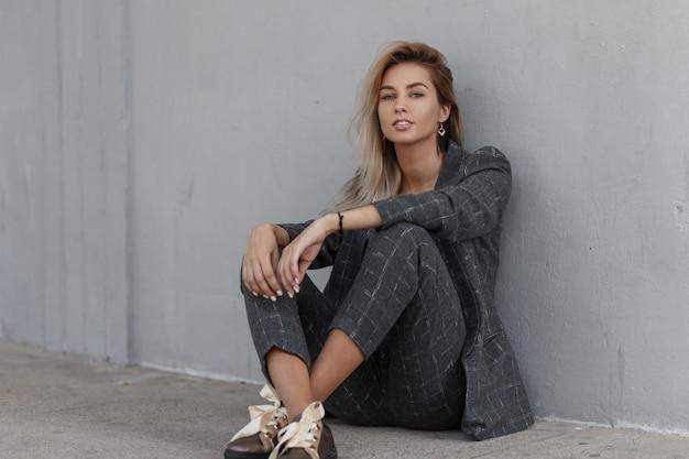 Giovane bella modella donna in un abito vintage rigoroso grigio con una giacca alla moda e pantaloni si siede sulla strada vicino al muro grigio