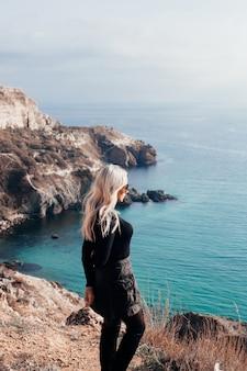 Giovane bella moda donna con capelli ondulati biondi guardando il mare
