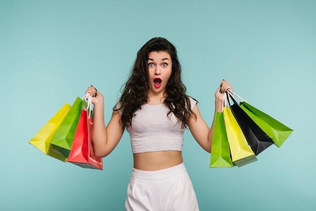 Giovane bella donna alla moda che tiene i sacchetti della spesa sopra il turchese