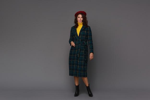 Giovane bella donna alla moda in cappotto autunno alla moda, berretto rosso e maglione giallo isolato su sfondo grigio.