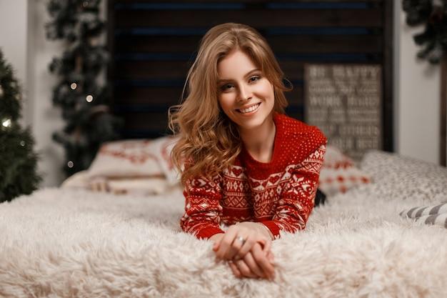 Giovane bella donna alla moda con una pettinatura in un maglione vintage si trova e riposa su un letto guardando la telecamera