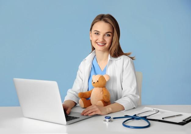 Giovane bella dottoressa al tavolo sulla parete