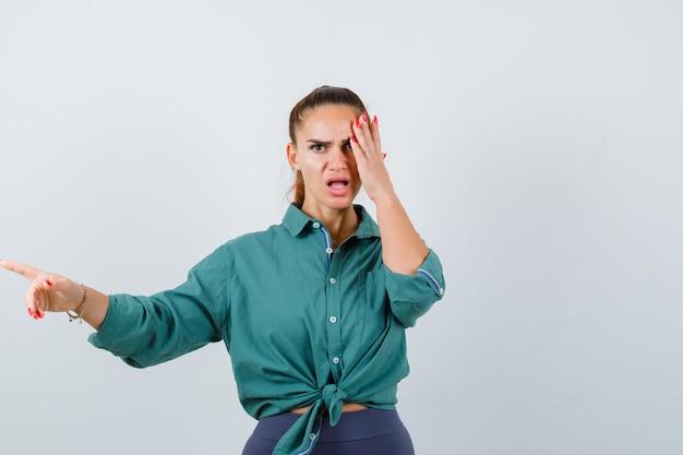 Giovane bella donna che punta lontano mentre tiene la mano sul viso in camicia verde e sembra arrabbiata, vista frontale.