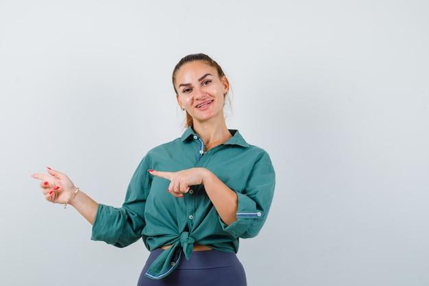 Giovane bella femmina che indica a sinistra in camicia verde e sembra beata. vista frontale.