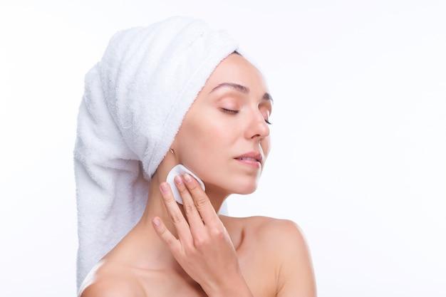 Giovane bella femmina con morbido asciugamano di cotone bianco sulla testa che applica il toner idratante sul viso dopo il bagno
