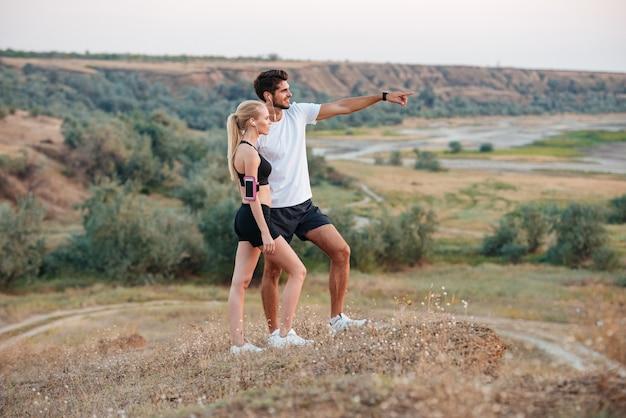 Coppia giovane bella fitness in piedi su una collina e guardando qualcosa