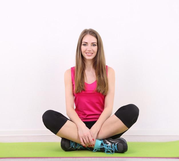 Giovane bella ragazza di forma fisica che si esercita sulla stuoia verde, in palestra