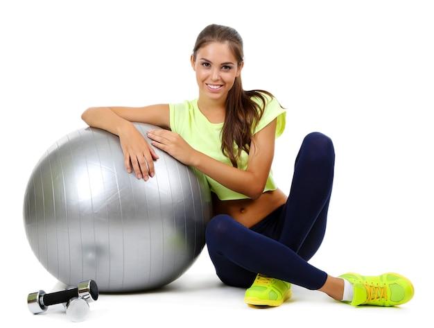 Giovane bella ragazza di forma fisica con balld grigio su bianco