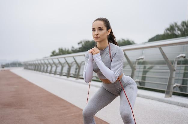 Giovane bella donna fitness in abbigliamento sportivo elegante allenamento all'aperto, facendo esercizi di squat con fascia di resistenza