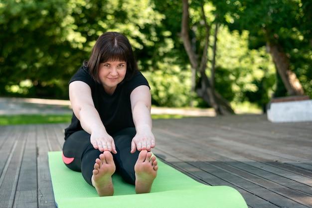 La giovane bella ragazza flessibile fa una piega in avanti con le mani da una posizione seduta. esercizi di stretching per principianti.