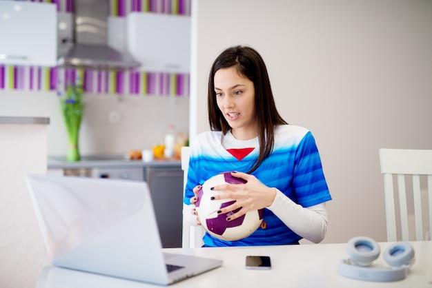 La giovane bella ragazza concentrata in maglia blu sta guardando una partita di calcio che incoraggia sul suo computer portatile.