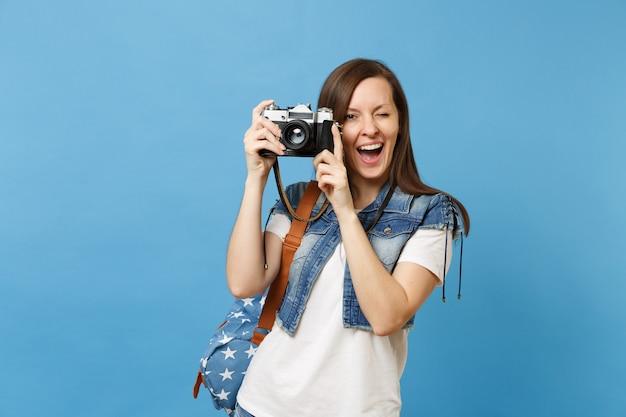 Giovane bella studentessa divertente in t-shirt, vestiti in denim con zaino lampeggiante che tiene retro macchina fotografica vintage isolata su sfondo blu. istruzione all'università. copia spazio per la pubblicità.