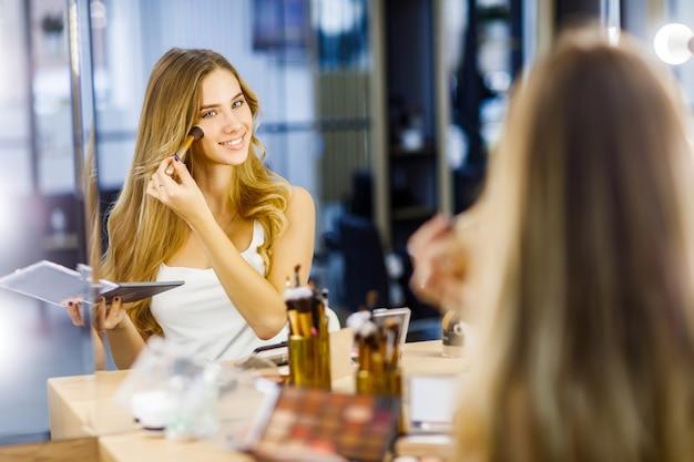 La giovane bella ragazza applica il rossore sul viso davanti allo specchio