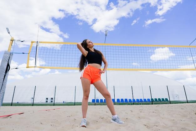 Atleta giovane, bella ragazza in abbigliamento sportivo si allena e corre, si allunga allo stadio
