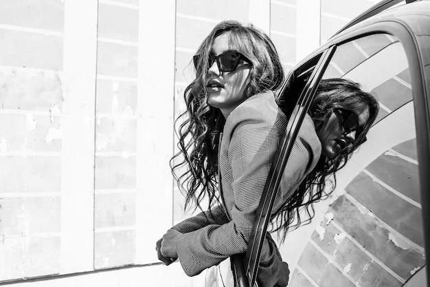 Una giovane e bella ragazza in un'auto nera guarda fuori dal finestrino. una ragazza alla moda con gli occhiali viaggia in macchina sporgendosi dal finestrino. foto in bianco e nero