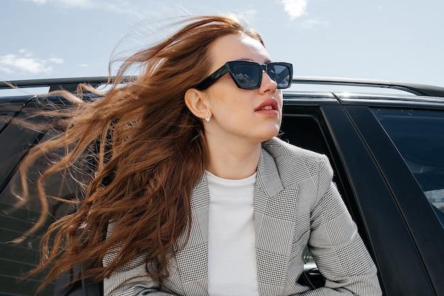 Una giovane e bella ragazza in un'auto nera guarda fuori dal finestrino. una ragazza alla moda con gli occhiali viaggia in macchina sporgendosi dal finestrino.