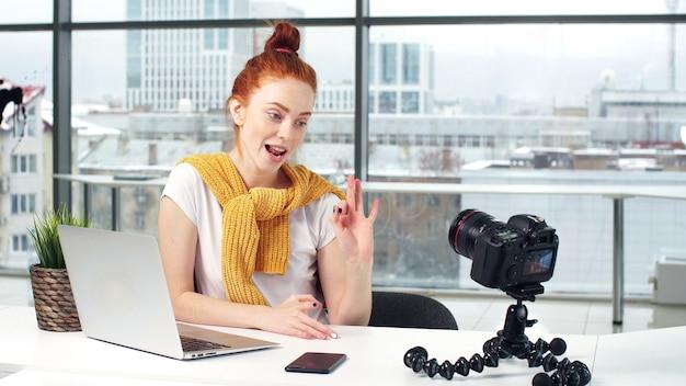 Una giovane bella ragazza blogger registra il suo blog su una fotocamera digitale