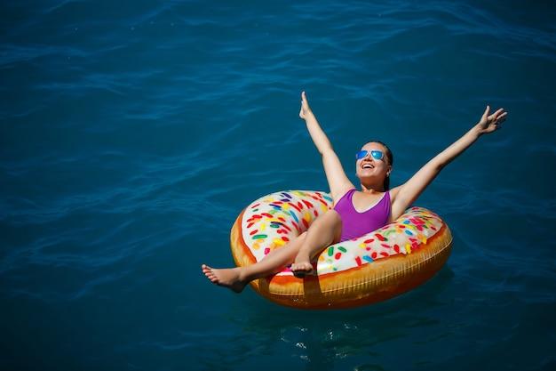 Una giovane bella ragazza in un costume da bagno luminoso giace su un grande anello gonfiabile e galleggia sul mare blu in una luminosa giornata estiva di sole