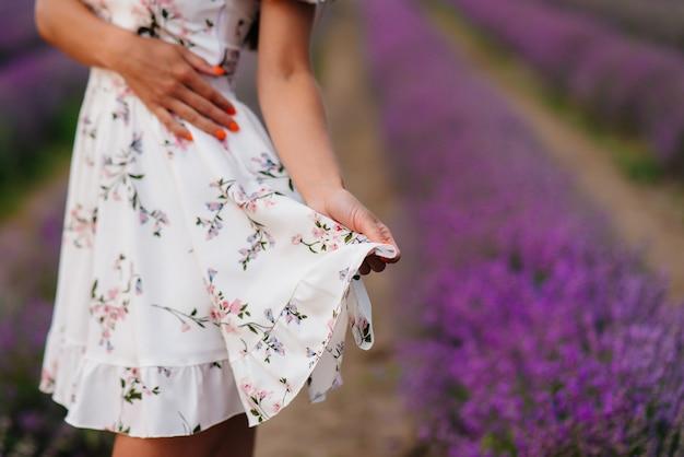 Una giovane bella ragazza in un vestito delicato e un cappello cammina attraverso un bellissimo campo di lavanda e gode dell'aroma dei fiori. vacanza e natura meravigliosa.