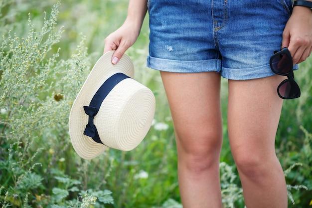 Giovane bella ragazza in salopette di jeans e un cappello leggero che cammina nel parco