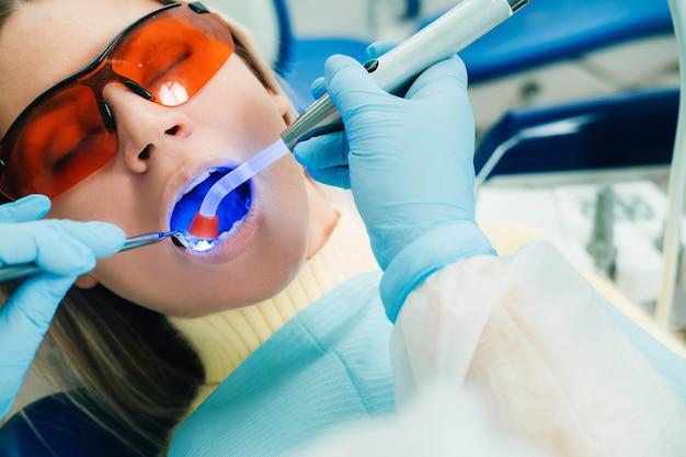 Una giovane bella ragazza in occhiali dentali tratta i suoi denti dal dentista con luce ultravioletta. file