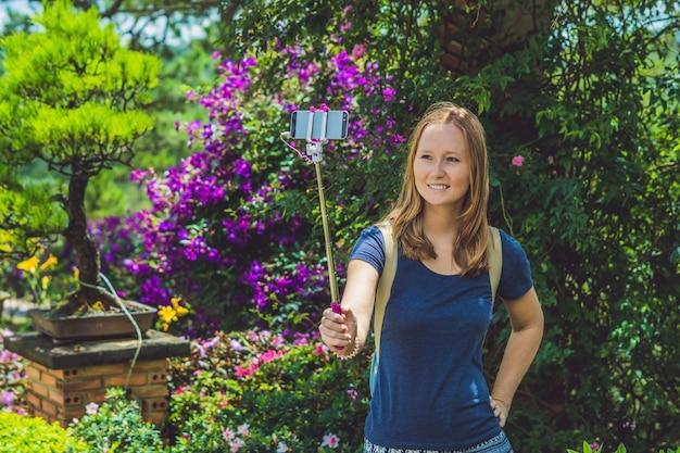 Giovane bella ragazza che fa selfie cellulare nel parco il giorno d'estate