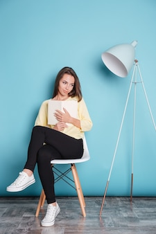Giovane bella ragazza che sogna qualcosa e tiene in mano un libro isolato sullo sfondo blu