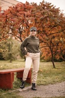 Giovane bella ragazza vestita con abiti eleganti, maglione verde e pantaloni beige, in un parco autunnale con bellissimi alberi