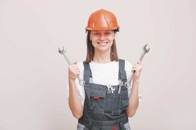 Giovane bella ragazza ingegnere in un'uniforme grigia e un casco protettivo sorride con strumenti, chiavi in mano.