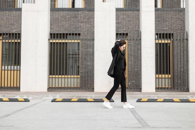 Giovane bella ragazza in abiti da lavoro alla moda con un blazer e scarpe da ginnastica bianche con occhiali da sole cammina in città vicino a un edificio moderno