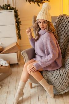 La giovane bella ragazza in un cappello di lana alla moda con un maglione lavorato a maglia vintage e calzini accoglienti si siede su una sedia e un plaid in un'atmosfera natalizia. vacanze invernali e stile