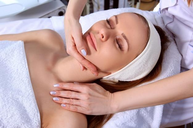 Giovane bella ragazza che ottiene trattamenti termali. medico che fa massaggio del viso.