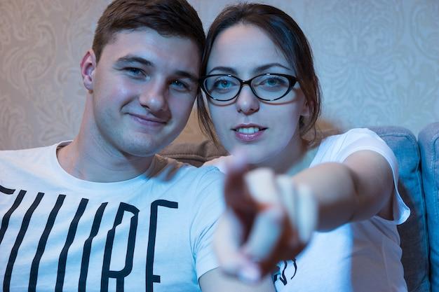 La giovane bella ragazza in vetri sta indicando la macchina fotografica che si siede su un divano con il suo ragazzo a casa guardando la televisione, vista frontale nel bagliore blu dal set