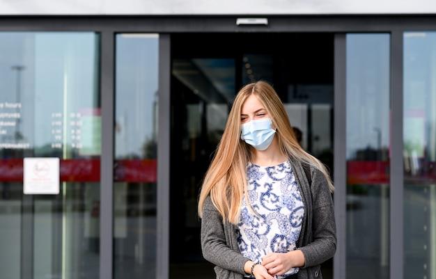 Giovane bella ragazza esce dal negozio con la maschera per il viso.