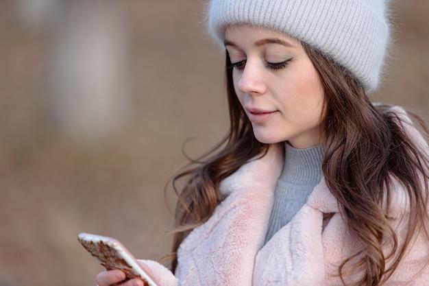 Giovane bella ragazza in un soffice cappello grigio e un cappotto rosa guarda lo smartphone.