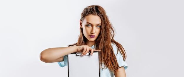 Giovane bella ragazza in possesso di un bordo di carte su uno sfondo grigio isolato. concetto di affari.
