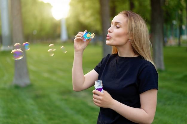 La giovane bella ragazza gonfia le bolle di sapone nel parco soleggiato dell'estate
