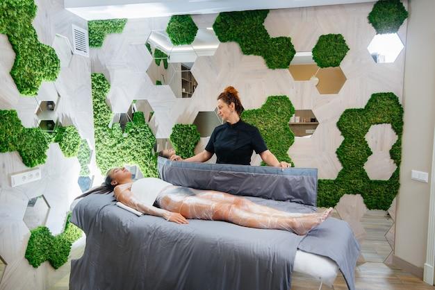 Una giovane bella ragazza sta facendo un impacco completo del corpo di procedura di cosmetologia in un moderno salone di bellezza procedure termali in un salone di bellezza.