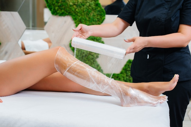 Una giovane bella ragazza sta facendo un impacco completo del corpo di procedura di cosmetologia in un moderno salone di bellezza. procedure termali in un salone di bellezza.