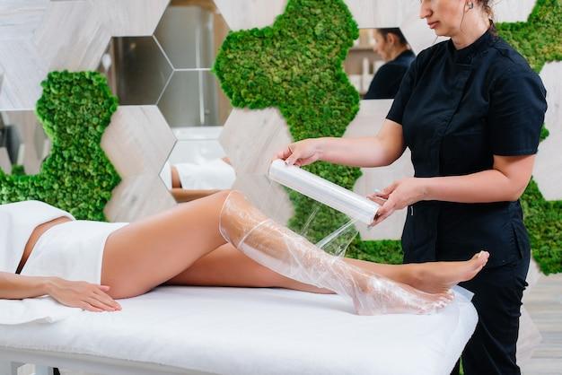 Una giovane bella ragazza sta facendo una procedura di cosmetologia avvolgente per il corpo in un moderno salone di bellezza