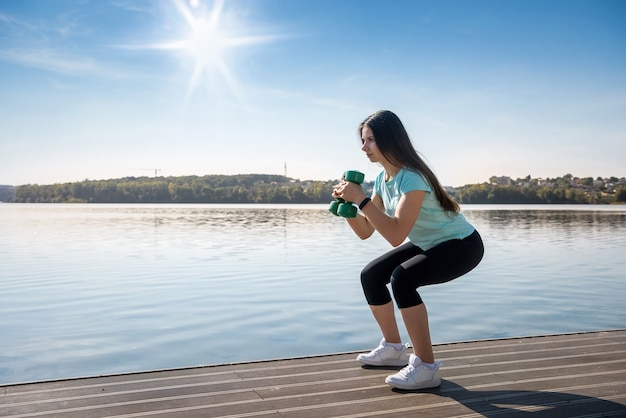La giovane bella ragazza è impegnata nella ginnastica mattutina con i manubri al lago