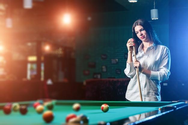 La giovane bella ragazza sta giocando a biliardo.