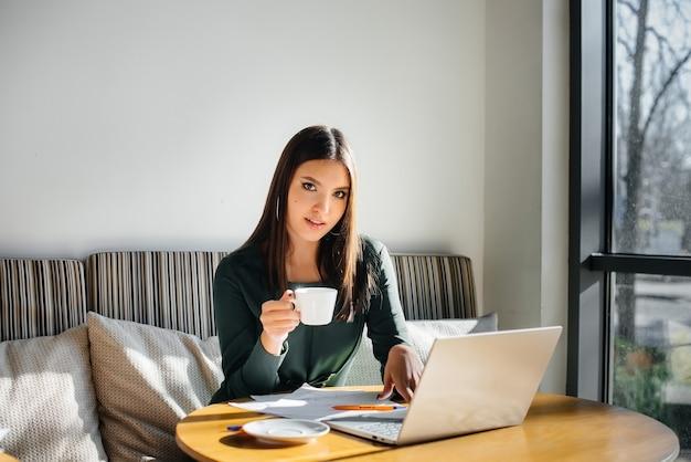 Una giovane bella ragazza è seduta in un bar, lavora al computer e comunica nei social network.