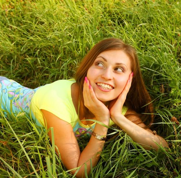 Giovane bella ragazza giace su un'erba