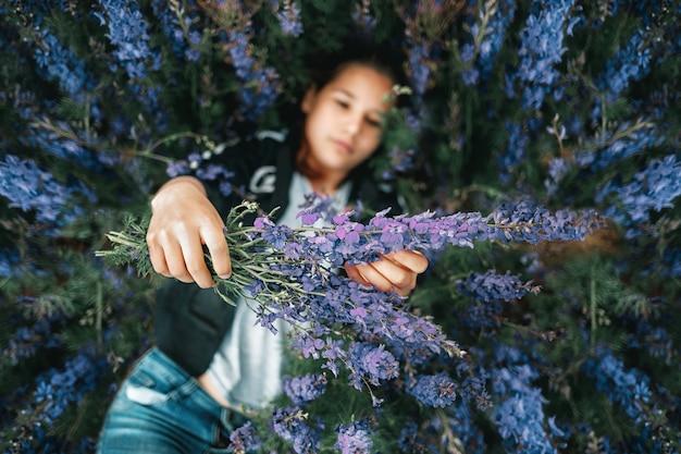 La giovane bella ragazza si trova sull'erba e tiene un mazzo di fiori viola nelle sue mani