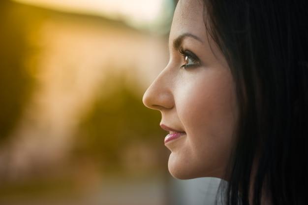 La giovane bella ragazza osserva nel profilo, primo piano. profili il ritratto di bella giovane donna che esamina una pagoda calda dalla finestra. primo piano sul viso, la gioia della pagoda solare.