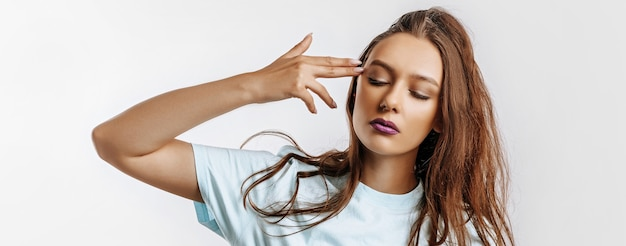 Una giovane bella ragazza fa un'imitazione di una pistola dalle sue dita. moda donna con labbra viola sul muro grigio isolato. brutti eventi, emozioni di disperazione e minacce