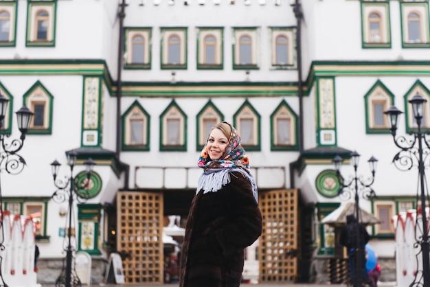 Una giovane bella ragazza con un cappotto di visone e una sciarpa popolare russa passeggia intorno al cremlino di izmailovo. mosca, russia.