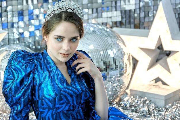 Modello di giovane bella ragazza con gli occhi azzurri che indossa un abito festivo blu in posa sullo sfondo di decorazioni di capodanno brillante come stelle in fiamme e sfere a specchio