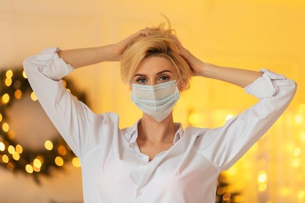 Modello di giovane bella ragazza con una maschera medica in una camicia casual bianca su uno sfondo di luce gialla bokeh